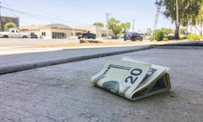 Cash lying on the sidewalk. (The Epoch Times)