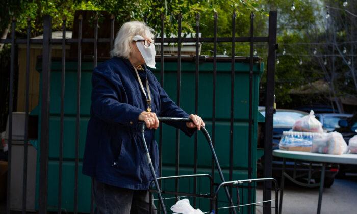An elderly woman wearing a napkin for a mask walks on a sidewalk near her home in Los Angeles, Calif., on June 22, 2020. (John Fredricks/The Epoch Times)