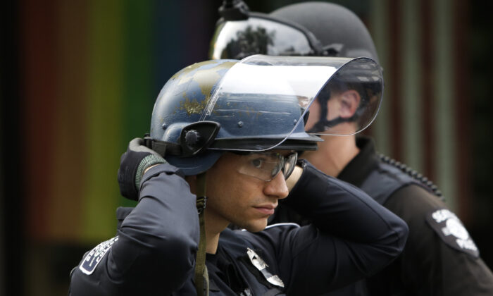 A police officer adjusts his helmet at a barricade outside the Seattle Police Department's East Precinct in Seattle, Wash., on June 2, 2020. (Jason Redmond/AFP/Getty Images)