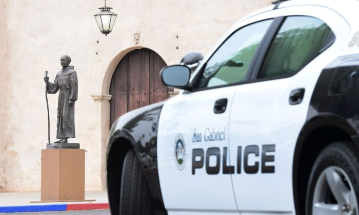A police vehicle is parked near a statue of Father Junipero Serra in front of the San Gabriel Mission in San Gabriel, Calif., on June 21, 2020.  (FREDERIC J. BROWN/AFP via Getty Images)