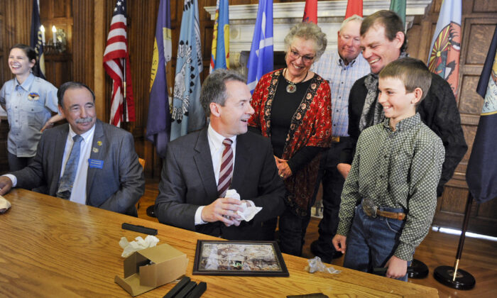 Montana Gov. Steve Bullock accepts a fossilized rib and tail vertebrae from a triceratops from Luke Phipps, 12, at the State Capitol in Helena, Mont., on April 16, 2016 (Thom Bridge/Independent Record/AP)