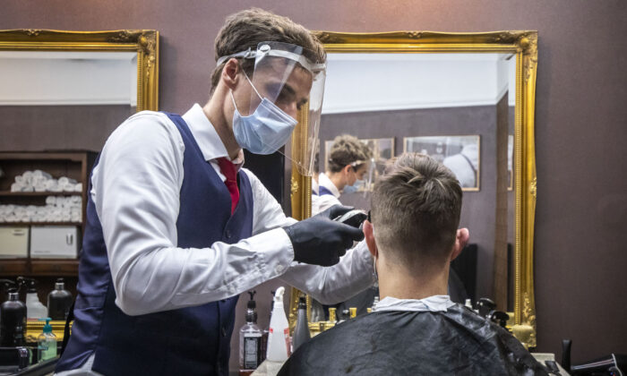 A barber wearing a face mask and protective shield gives a client a haircut at a barbershop in Prague, Czech Republic, on May 11, 2020. (Gabriel Kuchta/Getty Images)