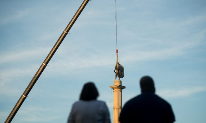 People look at the statue of John C. Calhoun atop the monument in his honor as workers prepare to relocate the memorial from Marion Square in Charleston, S.C., on June 24, 2020. (Sean Rayford/Getty Images)