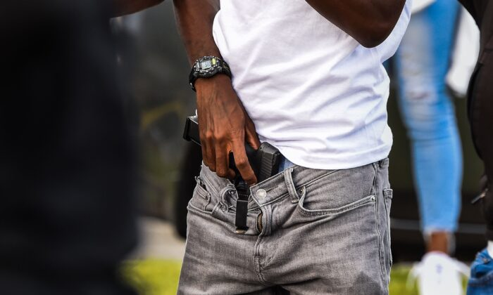 A man holds a gun as a group blocks the road next to a burned Wendy's restaurant in Atlanta, Ga., on June 16, 2020. (Chandan Khanna/AFP via Getty Images)