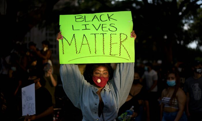 A woman wearing a facemask holds a placard during a demonstration in Houston, Texas on May 30, 2020. (Mark Felix/AFP/Getty Images)