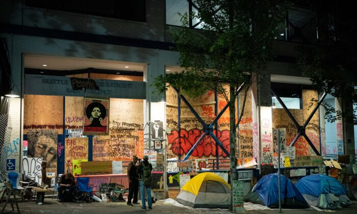 People stand near tents setup outside of the Seattle Police Department's vacated East Precinct in the area known as the Capitol Hill Organized Protest (CHOP) in Seattle, Wash. on June 23, 2020. (David Ryder/Getty Images)