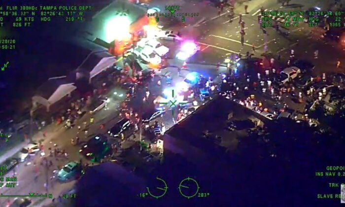 Police officers are surrounded after responding to a reported shooting that turned out to be a false report, according to police officers, in Tampa, Fla., early June June 20, 2020. (Tampa Police Department)