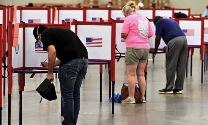 Voters fill out their ballots during in person voting in the Kentucky Primary at the Kentucky Exposition Center in Louisville, Ky., on June 23, 2020. (AP Photo/Timothy D. Easley)