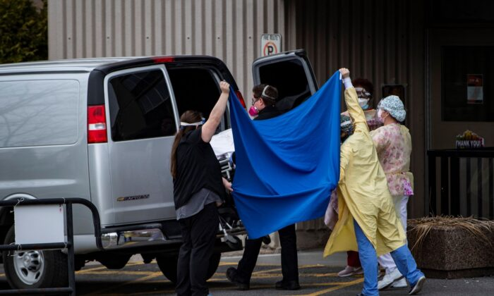 Healthcare workers use a sheet to obscure a person on a stretcher as the body is placed in an unmarked van outside the Laurier Manor in Ottawa, a long term care facility experiencing an outbreak of COVID-19, on April 26, 2020. (The Canadian Press/Justin Tang)