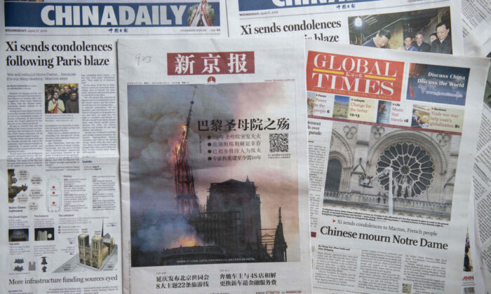 Front pages of the China Daily (L), the Beijing News (C) and the Global Times (R) featuring the Notre-Dame Cathedral disaster, in Beijing on April 17, 2019. (Nicolas Asfouri/AFP via Getty Images)
