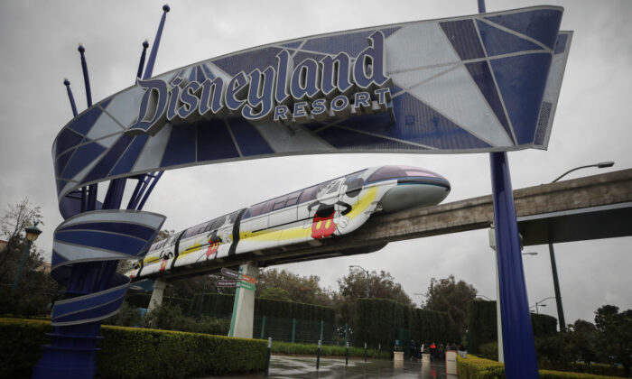 The monorail passes an entrance gate to the Disneyland amusement park in Anaheim, Calif., on March 13, 2020. (Mario Tama/Getty Images)