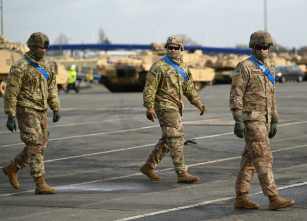 US soldiers walk alongside M1 Abrahams battle tanks from the U.S. 2nd Brigade Combat Team, 3rd Infantry Division, parked at Bremerhaven port on February 21, 2020 in Bremerhaven, Germany. The U.S. military is shipping military equipment from the United States to participate in the Defender 2020 international military exercises (David Hecker/Getty Images)