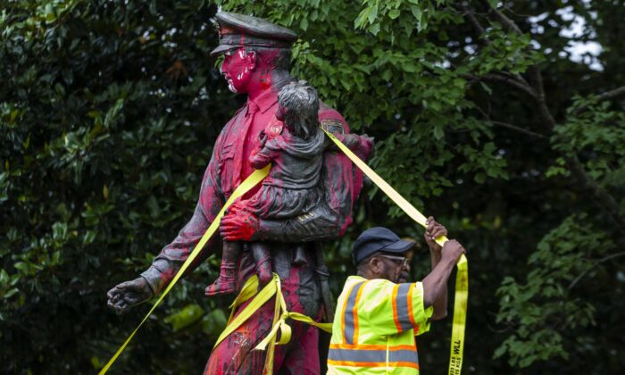 Workers remove a police memorial statue covered in red paint by protesters in Richmond, Va., on June 11, 2020. (Zach Gibson/Getty Images)