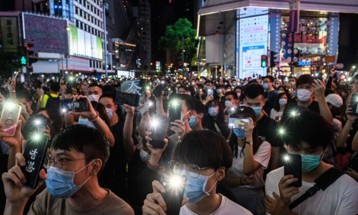Pro-democracy activists hold up their mobile phones as they sing during a rally in the Causeway Bay district of Hong Kong on June 12, 2020.  (Anthony Wallace/AFP via Getty Images)