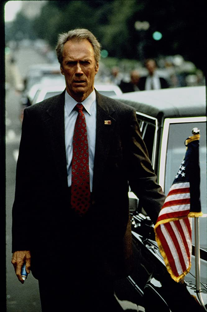 """man in suit with red tie, limosine, and America flag in """"In the Line of Fire"""""""