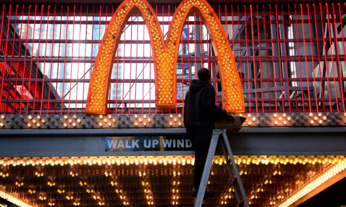 A worker changes light bulbs at a McDonald's front entrance on 42nd street near Times Square in New York City, on Jan 29, 2013. (Emmanuel Dunand /AFP via Getty Images)