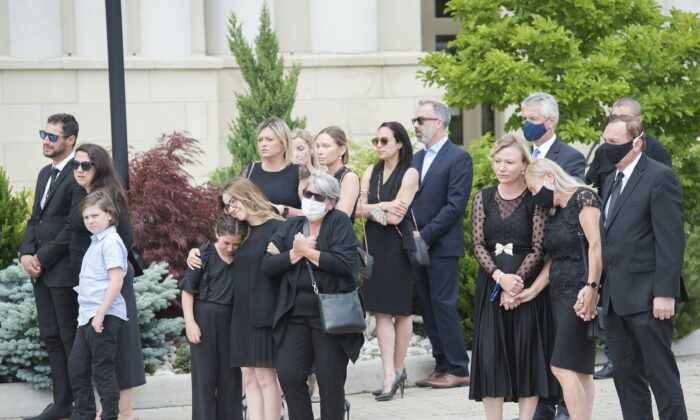Immediate family members react as they watch the arrival of the caskets of Karolina Ciasullo and her three young daughters, six-year-old Klara Ciasullo, four-year-old Lilianna Ciasullo, and one-year-old Mila Ciasullo in Brampton, Ont., on June 25, 2020. (Nathan Denette/The Canadian Press)