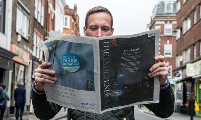 A man reads the last ever print edition of The Independent On Sunday newspaper, in London, England, on March 20, 2016. (Chris Ratcliffe/Getty Images)