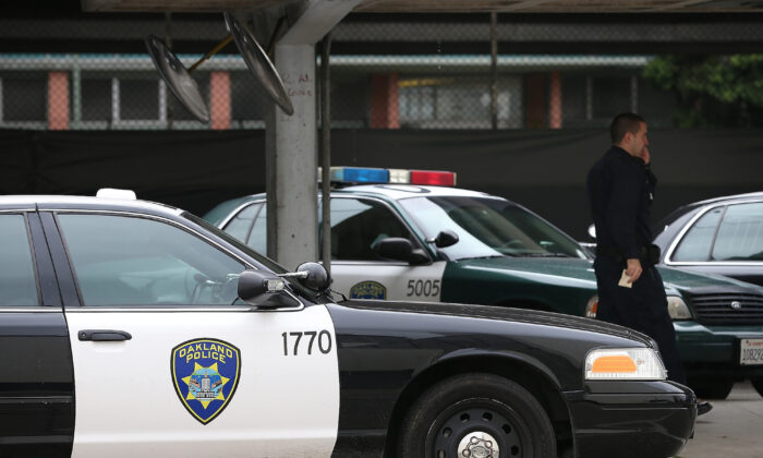 A police officer walks by patrol cars at the Oakland Police headquarters in Oakland, Calif., on Dec. 6, 2012. (Justin Sullivan/Getty Images)