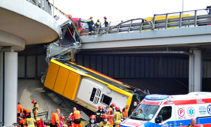 First responders treat the injured at the scene of a public bus crash, where the bus fell from a viaduct on the Armia Krajowa route in Warsaw, Poland, on June 25, 2020.(Agencja Gazeta/Dariusz Borowicz via Reuters)