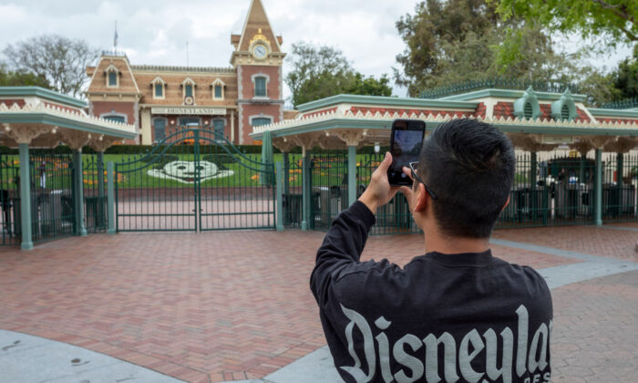 A man takes a photo outside the gates of Disneyland Park on the first day of the closure of Disneyland and Disney California Adventure theme parks due to the spread of COVID-19 in Anaheim, Calif., on March 14, 2020. (David McNew/AFP via Getty Images)