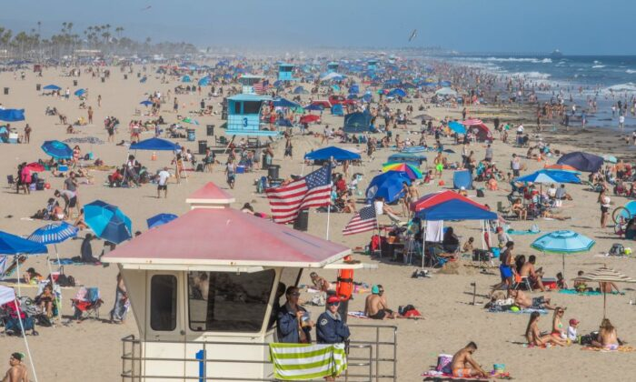 People enjoy one of Orange County's most popular beaches in Huntington Beach, Calif., on June 14, 2020. (Apu Gomes/AFP via Getty Images)