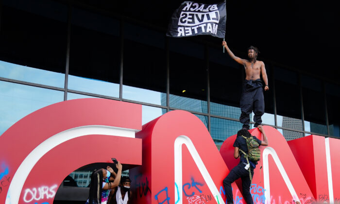 A man waves a Black Lives Matter flag atop the CNN logo during a protest in response to the police killing of George Floyd outside the CNN Center in Atlanta, Ga., on May 29, 2020. (Elijah Nouvelage/Getty Images)