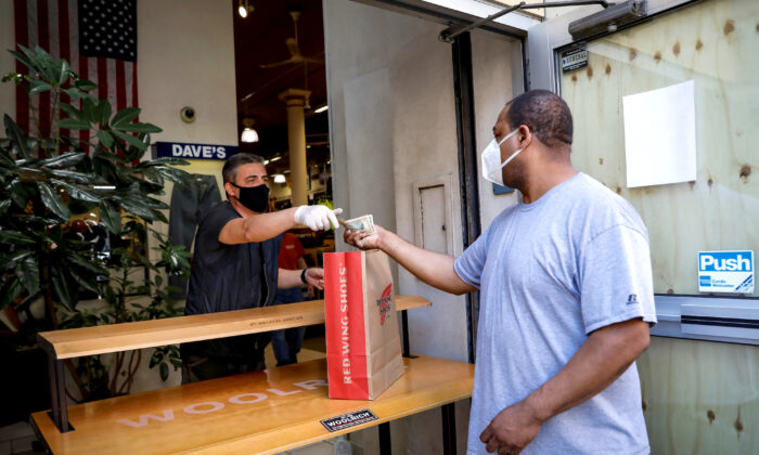 A customer pays for his purchase in the doorway of Dave's New York, a retail store, in New York City, on June 8, 2020. (Brendan McDermid/Reuters)