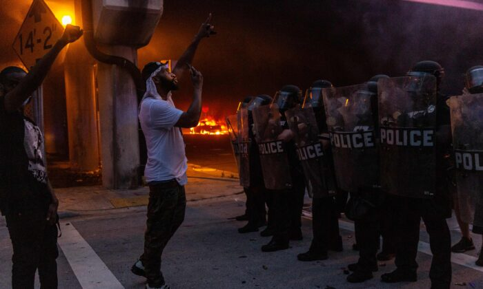 Protesters confronts riot police in front of a burning police car during a protest against police brutality in Miami, Fla., on May 30, 2020. (Adam DelGiudice/AFP via Getty Images)