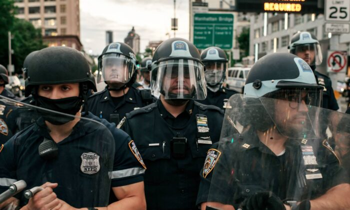 NYPD officers block the entrance of the Manhattan Bridge as hundreds protesting alleged police brutality and systemic racism attempt to cross into the borough of Manhattan from Brooklyn after a citywide curfew went into effect in New York City on June 2, 2020. (Scott Heins/Getty Images)