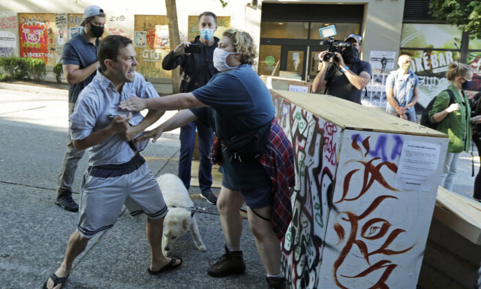 A person tries to take away a hammer from a man at left who was using it to remove artwork on barricades at the CHOP (Capitol Hill Occupied Protest) zone in Seattle, Wash., on June 26, 2020. (Ted S. Warren/AP Photo)
