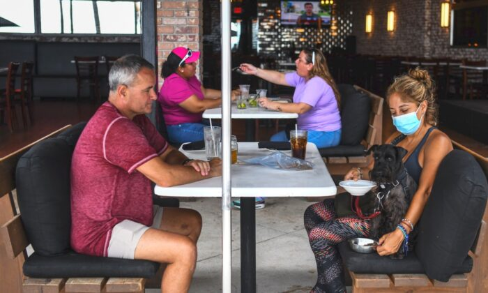 People eat sitting outside of a restaurant on Fort Lauderdale Beach Boulevard in Fort Lauderdale, Fla., on May 18, 2020. (Chandan Khanna/AFP via Getty Images)