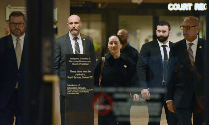 Huawei chief financial officer Meng Wanzhou, after a short morning session that ended the fourth day of trial in her extradition case, leaves British Columbia Supreme Court in Vancouver, Canada, with her security detail on Jan. 23, 2020. (Don Mackinnon/AFP via Getty Images)