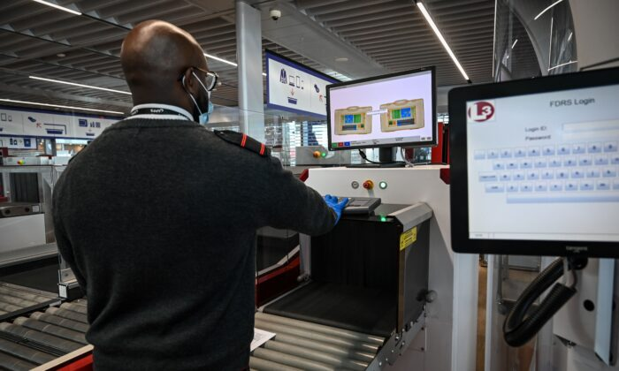 An airport staff member checks passengers' luggage passing through an X-ray machine at the Terminal 3 of the Orly airport, in Orly, on the outskirts of Paris, on June 22, 2020. (BERTRAND GUAY/AFP via Getty Images)