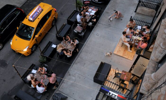 People eat outside of LENA Winebar as restaurants are permitted to offer al fresco dining as part of phase 2 reopening during COVID-19 outbreak in the Lower East Side neighborhood of Manhattan in New York City, N.Y., on June 27, 2020. (Andrew Kelly/Reuters)