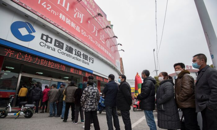 Customers line up to have their temperatures taken before entering a bank in Nantong city, in Jiangsu Province, eastern China, on Feb. 25, 2020. (STR/AFP via Getty Images)