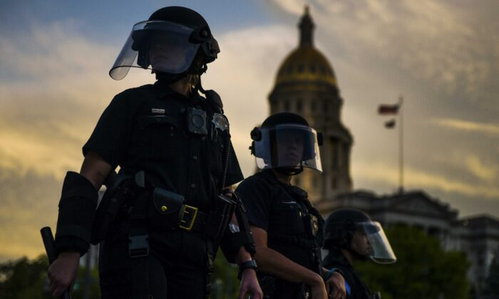 Police officers watch over a crowd of people near the Colorado state capitol during a protest in Denver, Col., on May 29, 2020. (Michael Ciaglo/Getty Images)