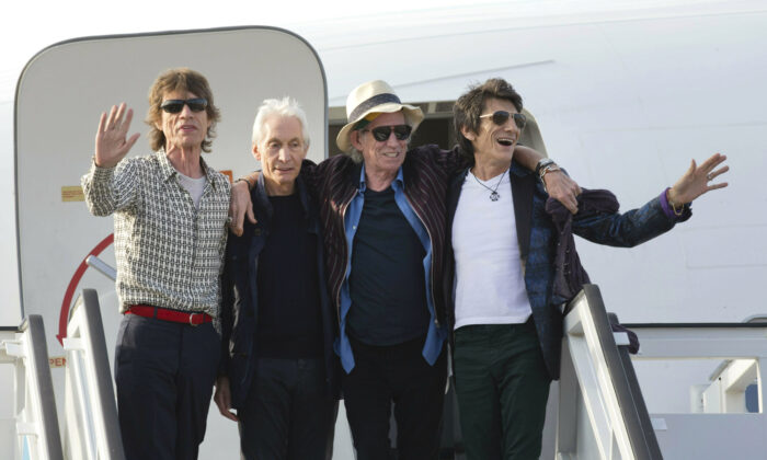 Members of The Rolling Stones, from left, Mick Jagger, Charlie Watts, Keith Richards and Ron Wood pose for photos from the plane that brought them to Cuba at Jose Marti international airport in Havana, Cuba, on March 24, 2016. (Ramon Espinosa/AP Photo)