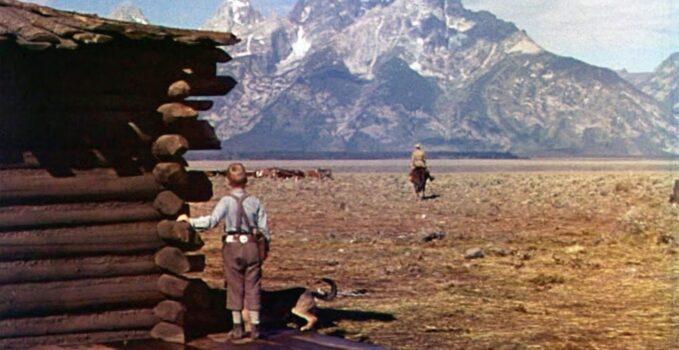 boy watching a man ride toward mountains