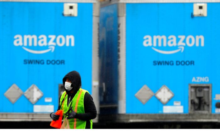 A worker in a face mask walks by trucks parked at an Amazon facility as the global coronavirus (COVID-19) outbreak continued in Bethpage on Long Island in New York, on March 17, 2020. (Andrew Kelly/Reuters)