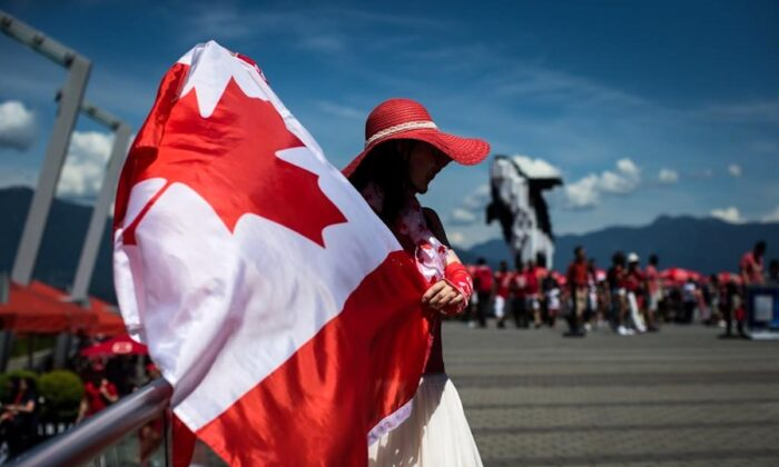 Summer Shen waves a Canadian flag while sporting a patriotic outfit during Canada Day celebrations in Vancouver, on July 1, 2019. (Darryl Dyck/The Canadian Press)