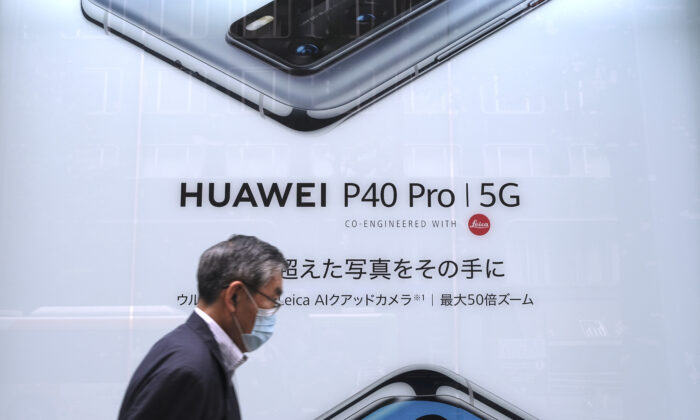 In this picture taken on June 27, 2020, a man walks past an advertisement for the latest smartphone by Chinese telecommunications company Huawei in Tokyo. (KAZUHIRO NOGI/AFP via Getty Images)