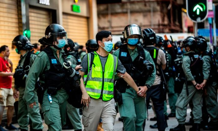Police arrest a man (C) and lead him to a nearby bus during a protest against China's planned national security law in Hong Kong on June 28, 2020. (Issac Lawrence/AFP via Getty Images)