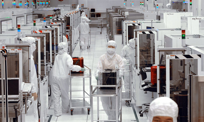 Engineers of United Microelectronics Corp (UMC) push trollies at the 12-inch UMC wafer factory in Tainan Science Park, Taiwan, on April 28, 2006. (Sam Yeh/AFP via Getty Images)
