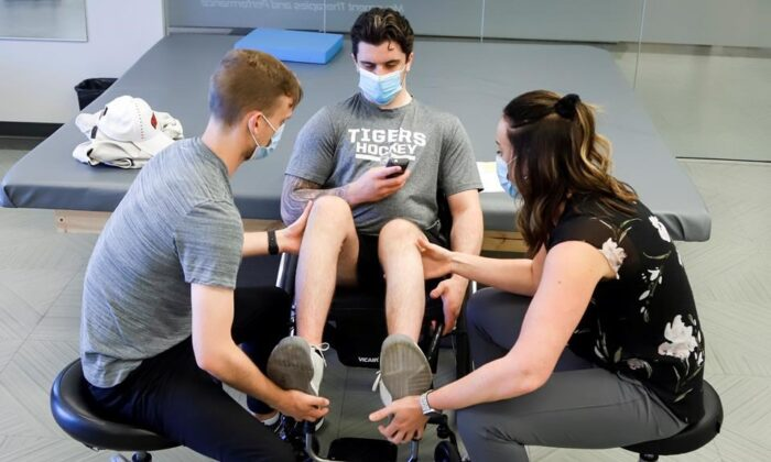 Humboldt Broncos bus crash survivor Ryan Straschnitzki (C) works out with the help of physiotherapists Jill Truman and Matthew Wright, during a training session in Calgary on June 25, 2020. (The Canadian Press/Jeff McIntosh)