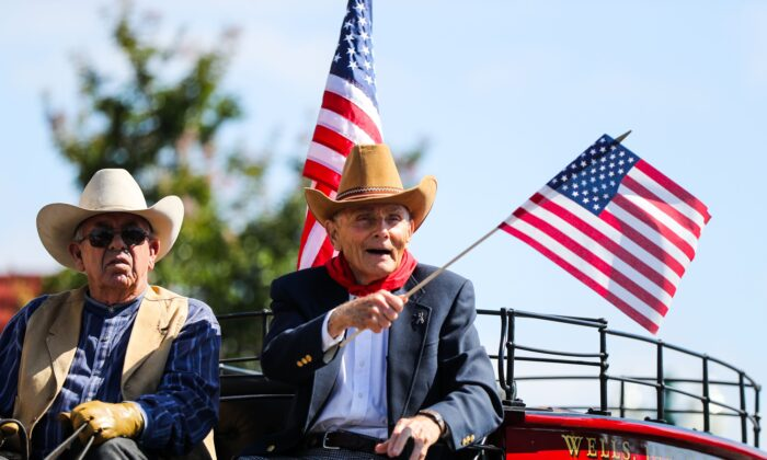 A man waves an American flag while riding a carriage at the Fourth of July parade, in Alameda, Calif., on Monday, July 4, 2016.(GABRIELLE LURIE/AFP via Getty Images)