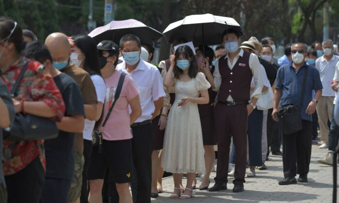People wait in line to undergo COVID-19 swab tests at a testing station in Beijing on June 30, 2020. (GREG BAKER/AFP via Getty Images)