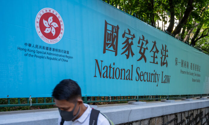 A pedestrian walks past a government-sponsored advertisement promoting a new national security law in Hong Kong on June 30, 2020. (Billy H.C. Kwok/Getty Images)