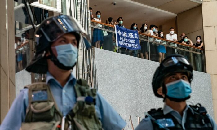 Pro-democracy supporters hold a Hong Kong Independence flag and shout slogans during a rally against the national security law as riot police secure an area in a shopping mall on June 30, 2020 in Hong Kong. Beijing has passed the controversial national security law which will threaten the city's autonomy and political freedoms. ( Anthony Kwan/Getty Images)