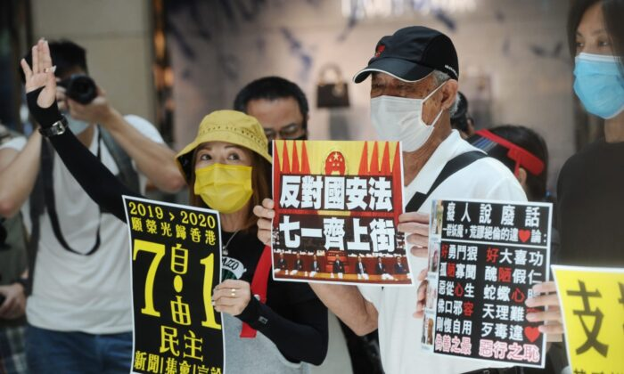 Protesters take part in a lunchtime protest in Central district, Hong Kong on June 30, 2020. They hold up signs calling on people to join a July 1 protest. (Song Bilung/The Epoch Times)
